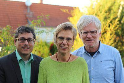 Das Bild zeigt drei Menschen: Links ein Mann mit Brille, in der Mitte eine Frau mit Brille, rechts ein Mann mit Brille. Im Hintergrund sind ein Haus und Bäume zu sehen. Herbstliche Stimmung.